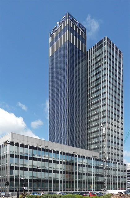 CIS Tower dengan menara perkantoran berlapis kaca di kanan dan menara berdinding solar panel di kiri.